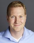 Portrett av mann med kort hår og blå skjorte. Foto.