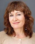 Portrett av kvinne med langt krøllete hår og beige strikkejakke. Foto.