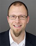 Portrett av mann med kort hår, skjegg, briller, hvit skjorte og sort dressjakke. Foto.