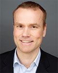 Portrett av mann med kort hår, blå skjorte og sort dressjakke. Foto.