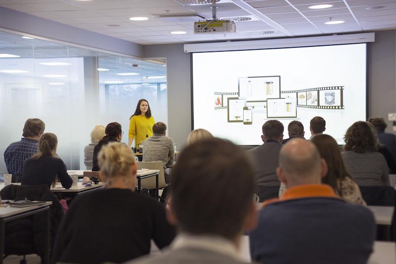 Kvinne som står foran en sittende forsamling og holder en presentasjon på skjerm. Foto