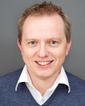 Portrett av mann med kort hår, hvit skjorte og blå genser. Foto.