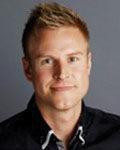 Portrett av mann med kort lyst hår og sort piqueskjorte. Foto