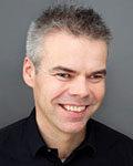 Portrett av mann med kort hår og sort genser. Foto.