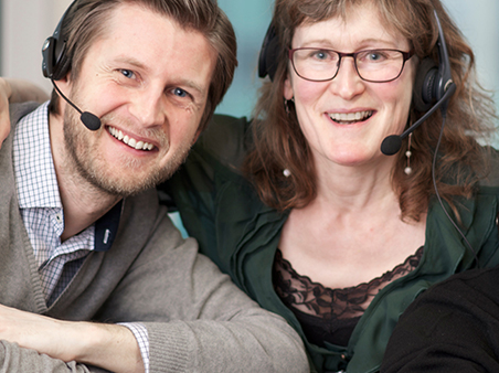 Blid dame og mann med headsett. Foto.