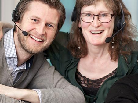 Blid mann og kvinne med headsett. Foto