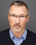 Portrett av mann med kort hår, briller, skjegg, blå skjorte og sort genser. Foto.