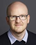 Portrett av mann med briller, blå skjorte og sort genser. Foto.
