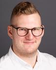 Mann med kort hår, briller og hvit skjorte. Foto.