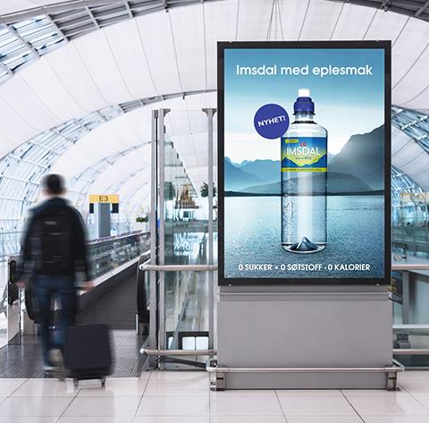 Reklameboard med bilde av Imsdal vann på flyplass. Grafikk.
