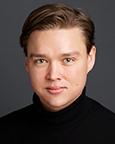 Portrett av ung mann i sort høyhalset genser. Foto.
