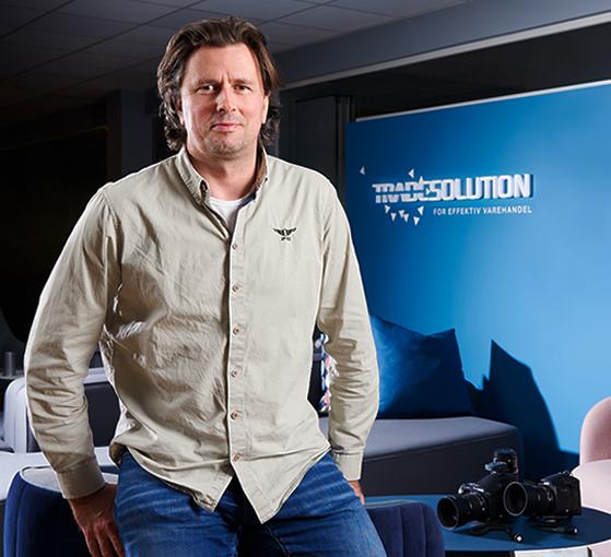 Mann som sitter på et bord med Tradesolution logo og kameraer i bakgrunnen. Foto.