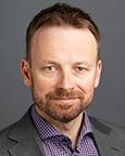 Portrett av mann med rutete skjorte og dressjakke. Foto.
