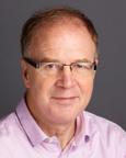 Mann med kort hår, briller og rosa skjorte. Foto.