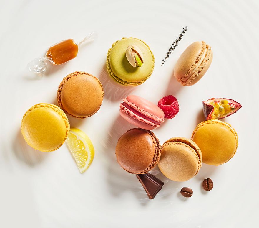 Fargerike makroner, frukt og sjokolade på hvitt underlag. Foto.