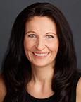 Portrett av kvinne med langt mørkt hår og sort singlet. Foto.