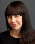 Portrettfoto av kvinne med langt mørkt hår og sort genser. Foto
