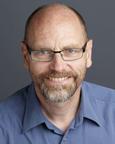 Portrett av mann med briller og blå skjorte. Foto.