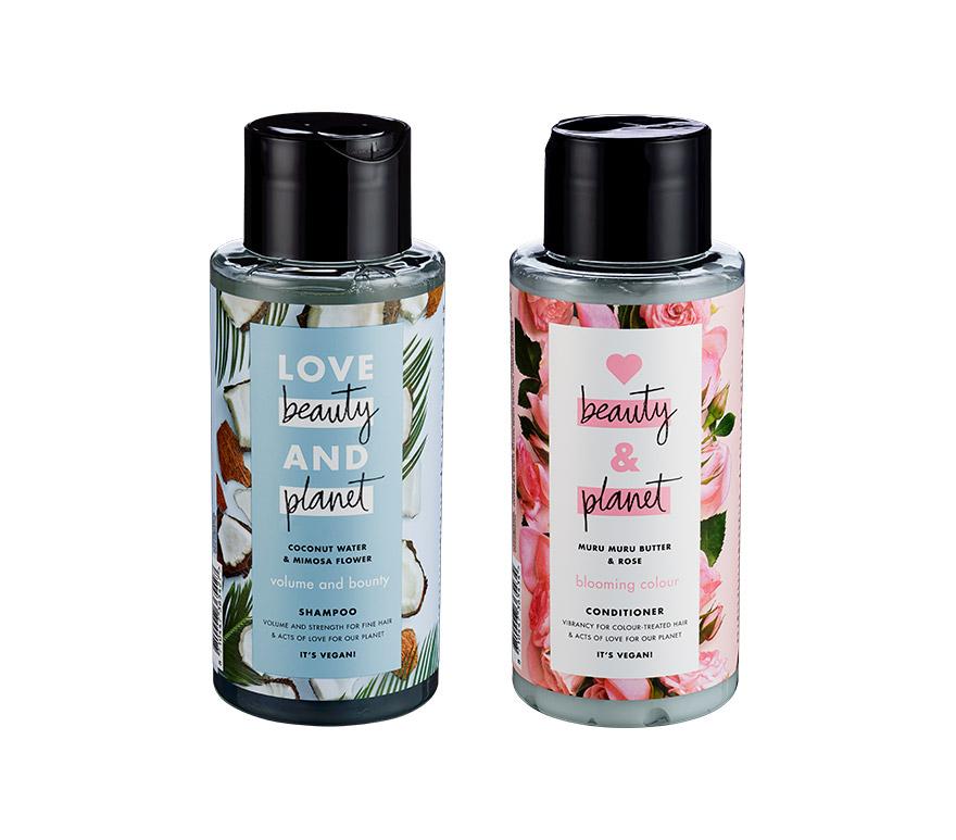 Blå flaske med shampo og rosa flaske med conditioner. Foto