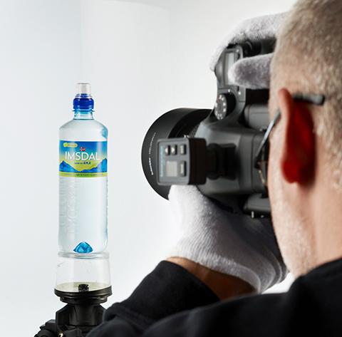 Fotograf bak profesjonelt kamera fotograferer Imsdal vannflaske. Foto.
