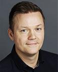 Portrett av mann med mørkt hår og sort genser. Foto.