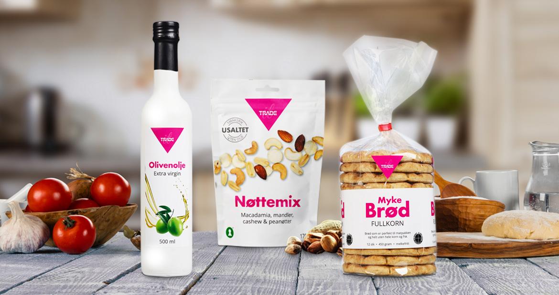 Miljøbilde av olivenolje, nøttemiks og myke brød på et bord med garnityr. Foto.