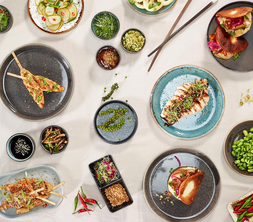 Gruppebilde av eksotiske matretter på tallerkener på et bord. Foto.