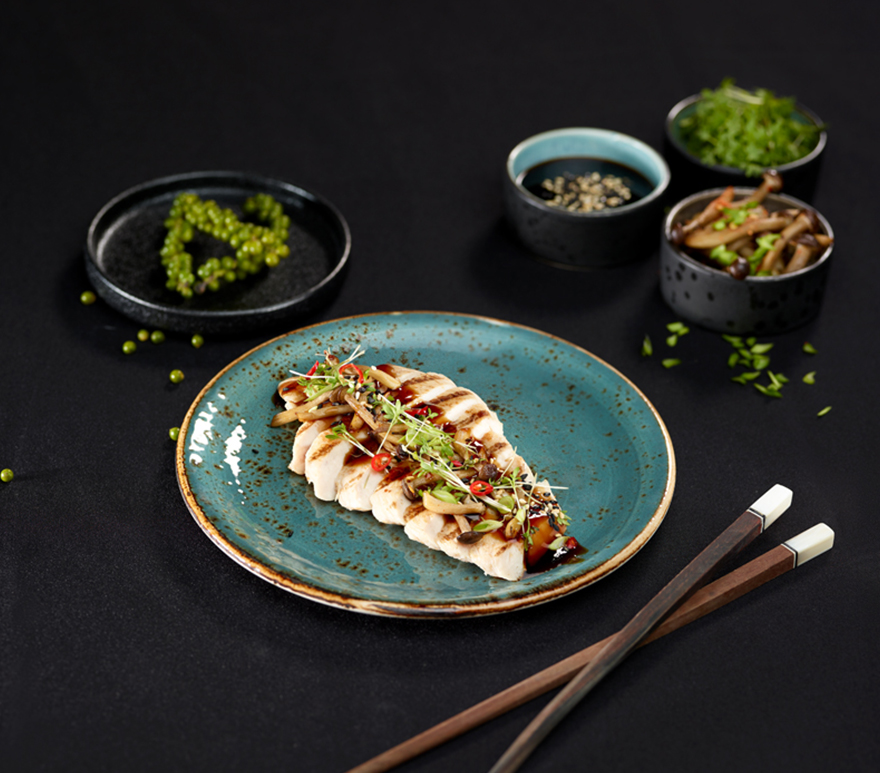 Hvit fisk tilberedt med urter på en tallerken på sort bord. Foto.