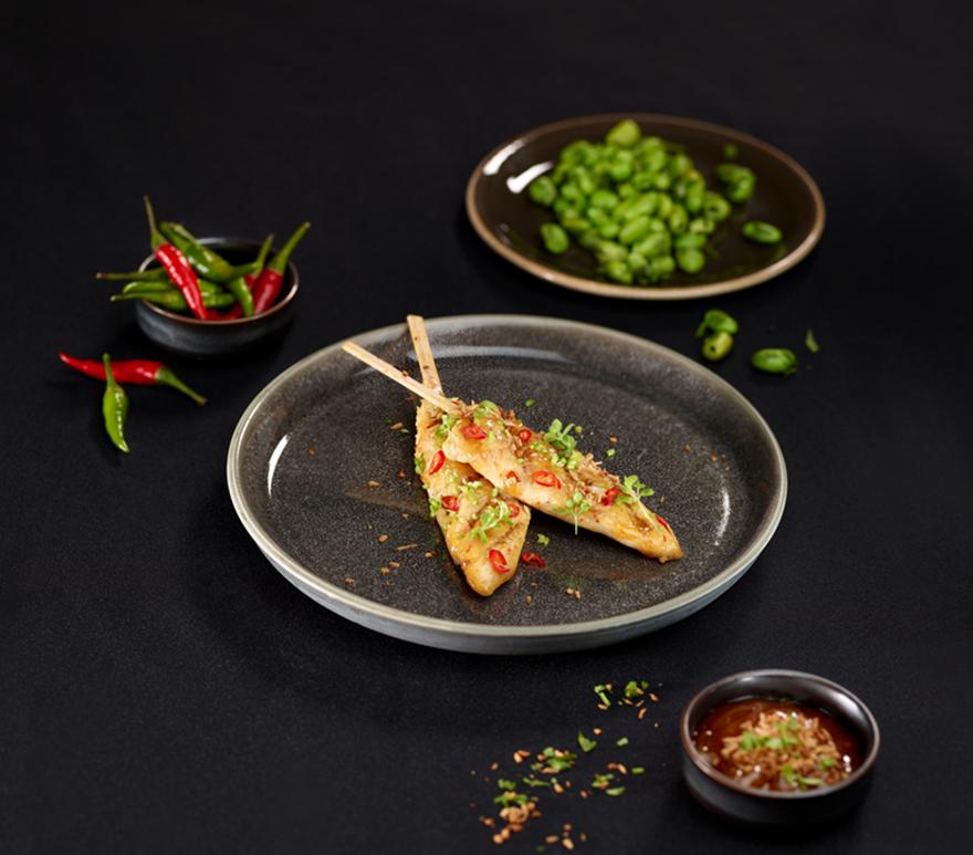 Kyllingspyd, grønne bønner og chili på en tallerken. Foto.