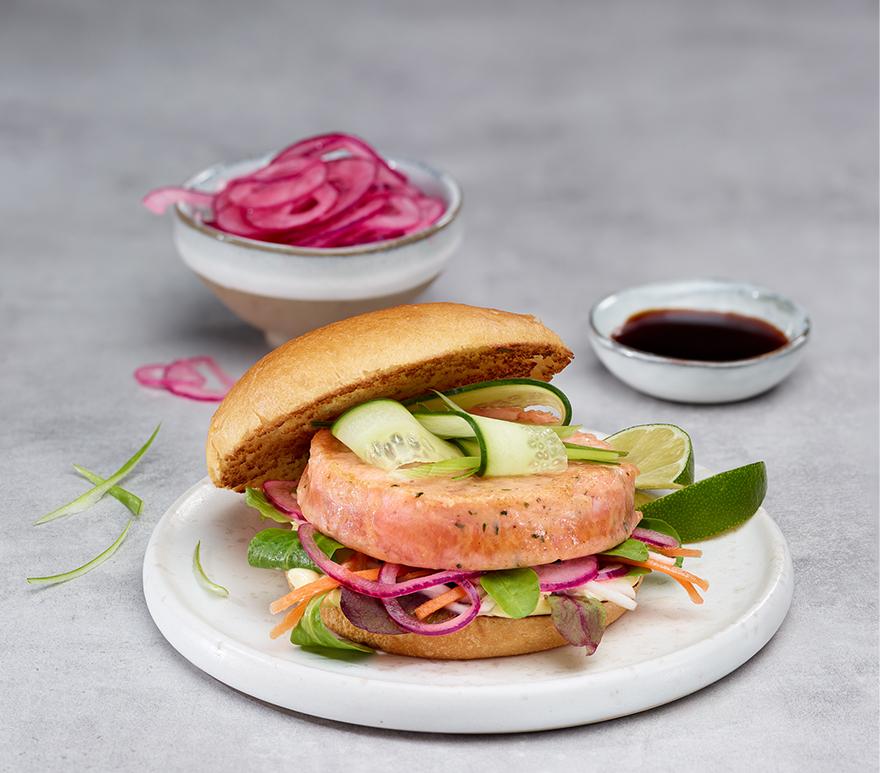 Lakseburger på en tallerken og grått underlag. Foto.