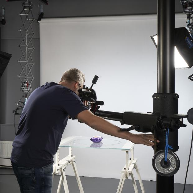 Fotograf i profesjonelt fotostudio fotograferer lilla produkt på glassbord. Foto.
